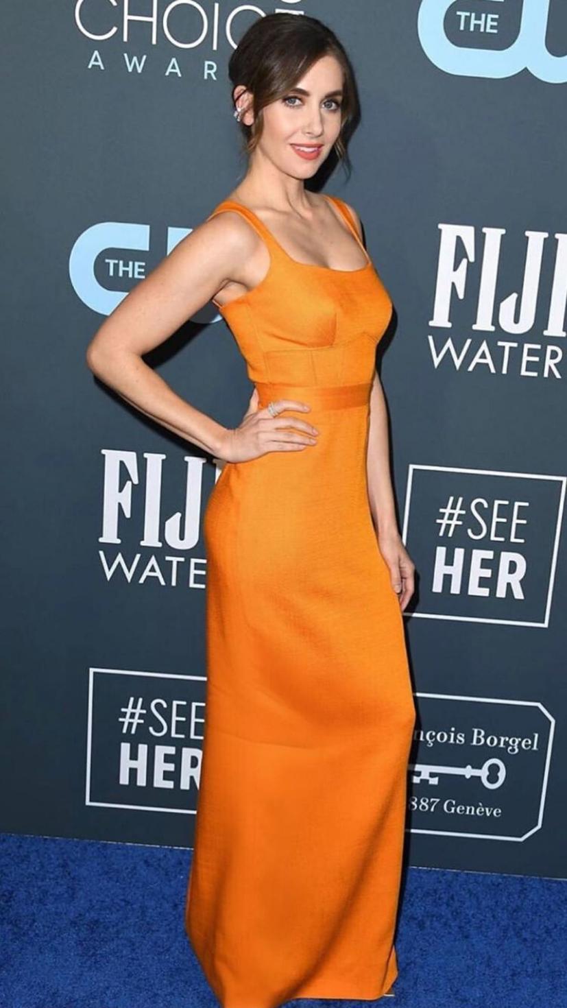 Alison Brie wears an orange Brandon Maxwell dress, Ana Khouri jewels, and Gianvito Rossi shoes.