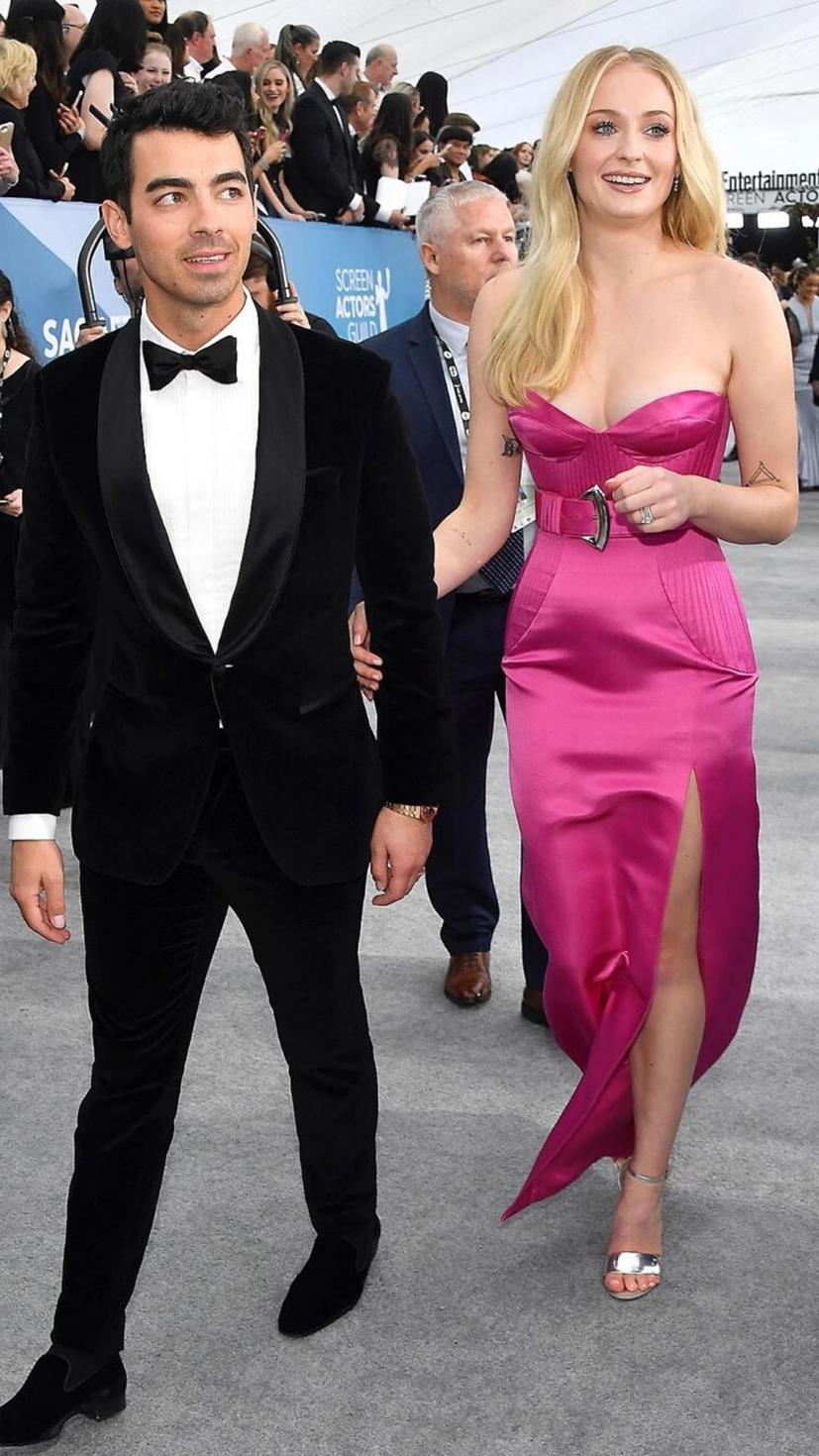 Sophie Turner wears a bright pink Louis Vuitton dress, while Joe Jonas opts for a Boss suit