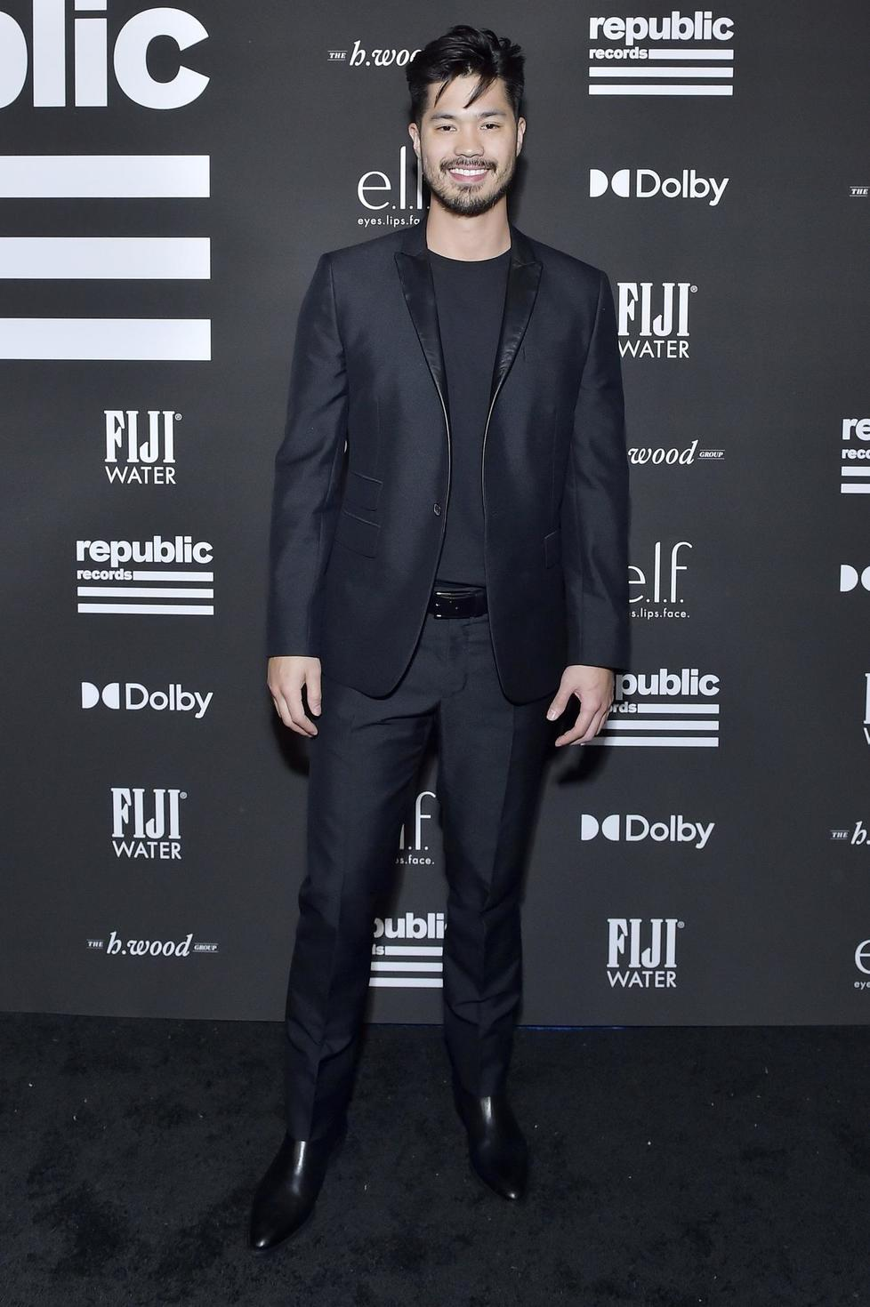 Ross Butler wears an all-black suit from Les Hommes and Kurt Geiger boots