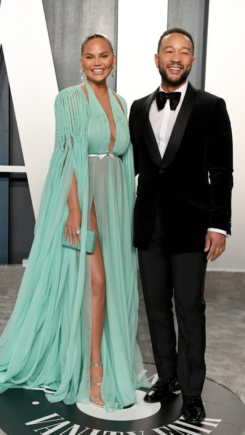 Chrissy Teigen wears Georges Hobeika S/S20 couture, and Heliopolis accessories. John Legend wears a Gucci tuxedo