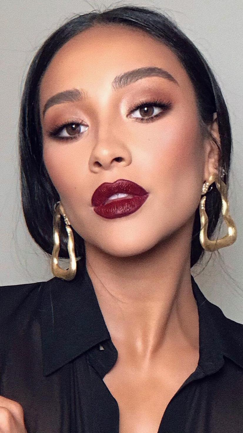 "If you didn't click next and go ""Whoa!"" then you're doing something wrong. This look is all about those wine-red lips, with light eyeshadow and mascara to accentuate it. A deep red-brown blush gives her cheekbones the attention they deserve."