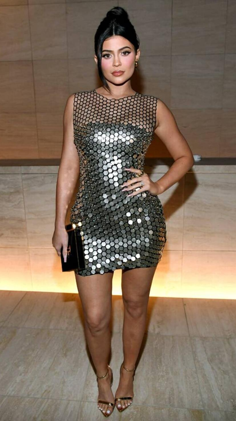 Kylie Jenner attending Tom Ford show wearing his designed silver dress and heels