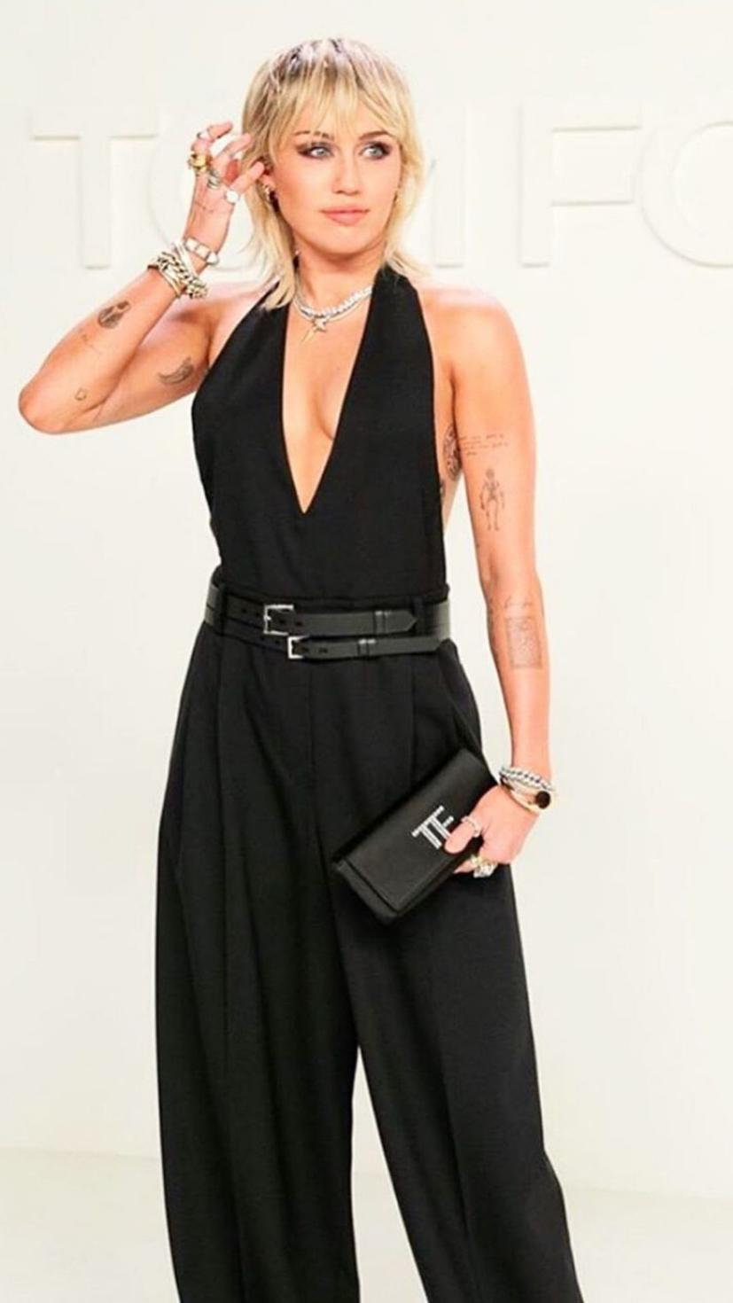 Miley Cyrus at the Tom Ford show wearing  jumpsuit and clutch from the brand